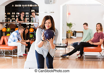 Young Woman Bowling in Club - Confident young woman bowling...