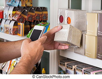 Mans Hand Scanning Product Through Mobile Phone - Cropped...