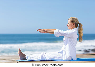 senior woman stretching on beach