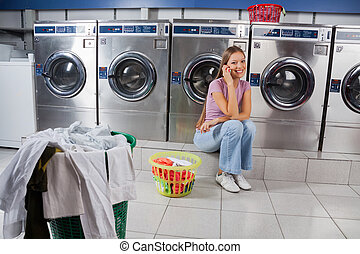 Beautiful Woman Using Mobile Phone At Laundry - Portrait...