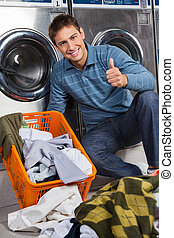Man Gesturing Thumbs Up At Laundry - Portrait of young man...