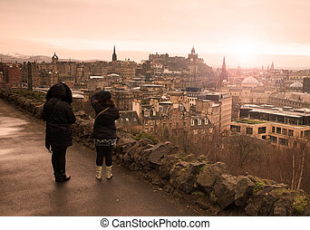 Two women watching the city of Edinburgh