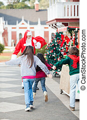 Children Running To Embrace Santa Claus - Rear view of...