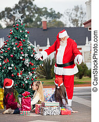 Santa Claus Gesturing At Children By Christmas Tree - Santa...