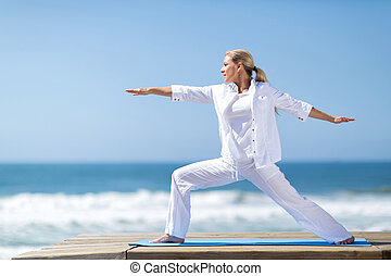 pretty middle aged woman yoga pose by the beach
