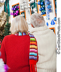 Senior Couple At Christmas Store - Rear view of senior...