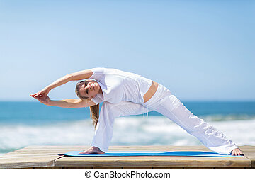 fit middle aged woman exercising on beach - fit middle aged...
