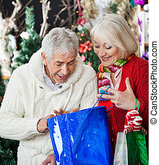 Surprised Couple Looking Into Shopping Bag