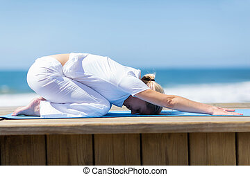 woman doing stretching exercise on beach