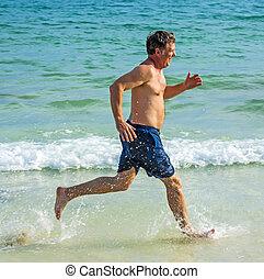 man runs along the beautiful beach