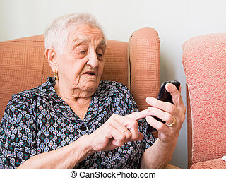 Old lady using a smartphone in her home