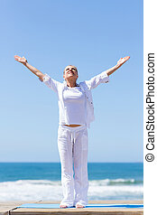 middle aged woman arms reach out on beach - healthy middle...