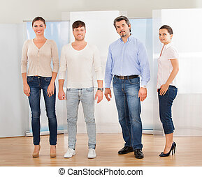 Happy Group Of People Standing Together On Hardwood Floor