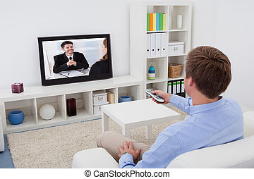 Man Watching Television - Rear View Of A Man Sitting On...