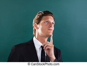 Young Thoughtful Businessman Looking Up - Portrait Of Young...