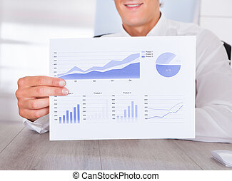 Businessman Holding Graph Printed On Paper - Close-up Of A...