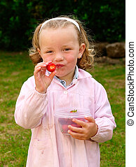 Little blonde girl eating strawberries outdoors