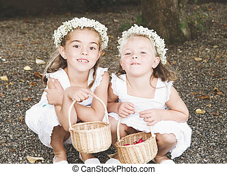 Two little girls dressed for a wedding. The girls are bowed,...
