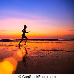 Silhouette of a woman jogger on the beach at sunset.