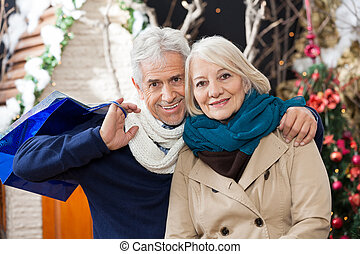 Couple With Shopping Bags At Christmas Store - Portrait of...