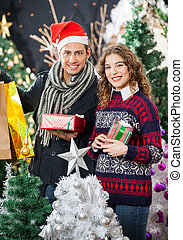 Couple Holding Christmas Presents At Store