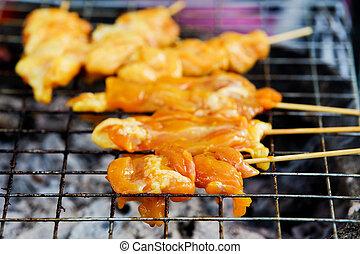 Satay chicken on grill.