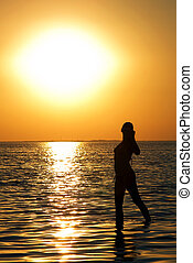 Silhouette of the young woman on a bay on a sunset