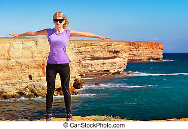 Woman Traveler standing outdoor hands raised to the blue sky with Sea and Rocks coastal on background Freedom and Healthy Lifestyle concept