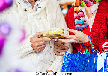 Couple Holding Christmas Present At Store - Midsection of...