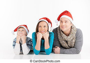Family on Christmas. Cheerful family in Santa hats looking...