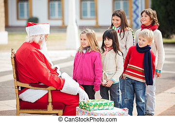 Santa Claus Looking At Children Standing In A Queue - Side...