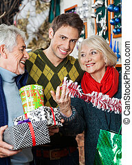 Man With Parents Shopping In Christmas Store - Portrait of...