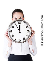 Business woman holding a clock in front of her face.