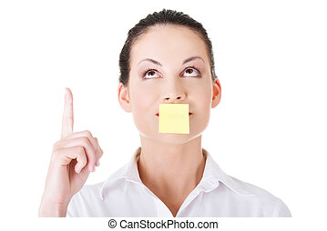 Beautiful woman with empty card on lips, pointing up.