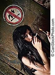 Beautiful young girl lights a cigarette near quot;No fire...
