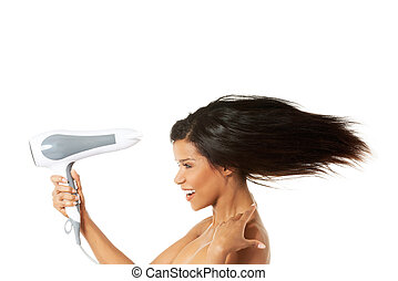 Attractive woman drying her hairIsolated on white