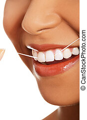 Attractive woman with dental floss. Closeup. Mouth and...
