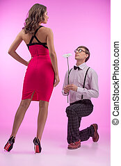 Nerd and beauty Young nerd man standing at his knee and...