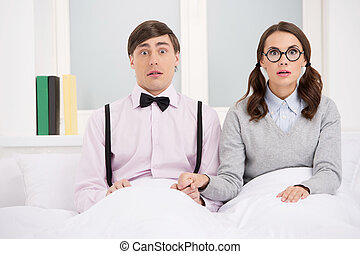 Nerd couple. Surprised nerd couple sitting on the bed and...