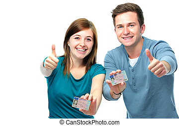 happy teens showing their driving license isolated over...