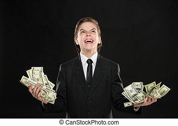 Power of the money Little boy in formalwear holding money in...