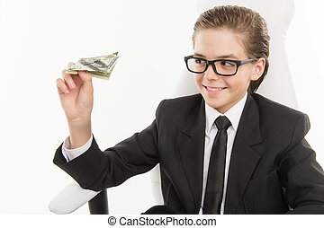 Bossy little businessman. Cheerful little boy in formalwear playing with paper airplane made from dollar while sitting at his working place