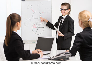Little boss and. Cheerful little boy pointing whiteboard while two women in formalwear looking at him