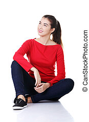 Happy casual woman sitting on the floor.