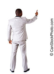 Young businessman pointing on copy space. back view.
