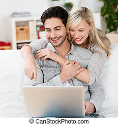 Happy young couple using a laptop computer as they relax at...