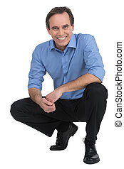 Executive crouching Cheerful mature businessman sitting...