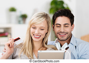 Happy online shoppers with an attractive young couple waving...