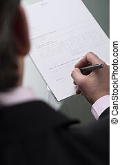 Signing an agreement. Top view of businessman signing a...