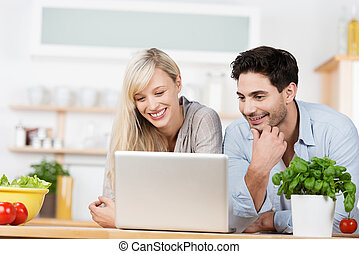 Young couple browsing the internet on a laptop computer as...